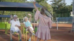 Menina feliz de sorriso pequena bonito com uma raquete de tênis em suas mãos que estão no campo de tênis que olha na câmera video estoque