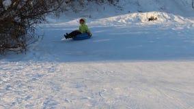 A menina feliz desliza no snowtube para baixo do monte no dia de inverno ensolarado video estoque