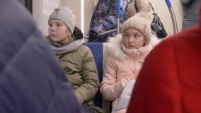 Menina feliz do adolescente dois que senta-se dentro do trem ao montar no metro da cidade vídeos de arquivo