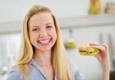 Menina feliz do adolescente que come o sanduíche na cozinha Fotos de Stock Royalty Free