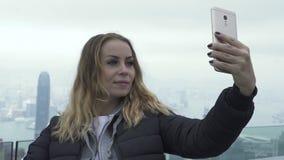 Menina feliz do curso que toma o panorama móvel da cidade de Hong Kong do selfie Mulher do turista que fotografa o retrato do sel filme