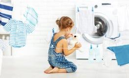 Menina feliz do divertimento da criança para lavar a roupa e o urso de peluche em l Imagens de Stock