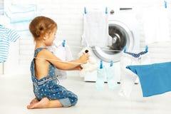 Menina feliz do divertimento da criança para lavar a roupa e o urso de peluche em l Fotografia de Stock