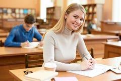 Menina feliz do estudante que aprecia o tempo na biblioteca fotos de stock