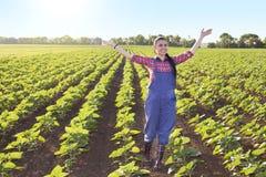 Menina feliz do fazendeiro no campo do girassol imagem de stock royalty free
