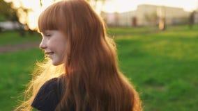 Menina feliz do gengibre que anda e que olha na câmera no por do sol no parque do verão filme