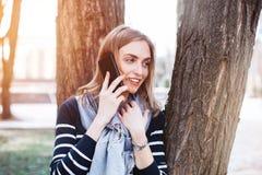 A menina feliz do moderno que tem a conversação de telefone celular agradável com noivo quando forem as caminhadas no parque da m Imagem de Stock