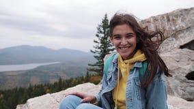 Menina feliz do moderno do viajante com cabelo ventoso e estar de sorriso sobre a montanha ensolarada cabelo à moda das mulheres video estoque