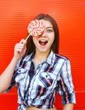 Menina feliz do retrato com o pirulito doce do caramelo que tem o divertimento imagem de stock royalty free
