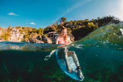 Menina feliz do surfista com prancha O surfista senta-se na placa no oceano fotografia de stock royalty free