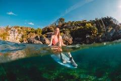 Menina feliz do surfista com prancha O surfista senta-se na placa no oceano fotografia de stock
