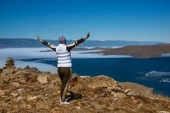Menina feliz do viajante com as mãos levantadas que estão sobre uma montanha acima do feriado do lago na primavera Fotos de Stock Royalty Free
