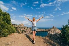 Menina feliz do viajante com as mãos levantadas que estão sobre uma montanha acima do mar nas férias de verão Imagens de Stock