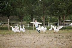 Menina feliz doce que corre após um rebanho dos gansos na exploração agrícola seus braços ao lado e ao sorriso Retrato do estilo  foto de stock