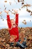 Menina feliz dos anos de idade sete que joga na pilha das folhas Fotografia de Stock