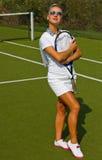 A menina feliz dos esportes está com a raquete na corte no dia de verão ensolarado Fotografia de Stock Royalty Free