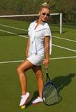A menina feliz dos esportes está com a raquete na corte no dia de verão ensolarado Fotos de Stock