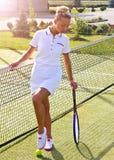 A menina feliz dos esportes está com a raquete na corte no dia de verão ensolarado Imagem de Stock