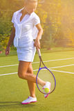A menina feliz dos esportes está com a raquete na corte no dia de verão ensolarado Fotos de Stock Royalty Free