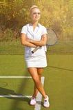 A menina feliz dos esportes está com a raquete na corte no dia de verão ensolarado Fotografia de Stock