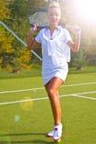 A menina feliz dos esportes está com a raquete na corte no verão ensolarado Fotografia de Stock Royalty Free