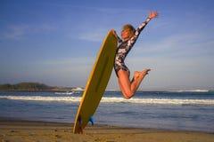 A menina feliz e atrativa nova do surfista que salta altamente no ar que guarda a placa de ressaca antes de surfar na praia tropi fotografia de stock