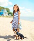 Menina feliz e cão de sorriso da criança que andam na praia no verão foto de stock