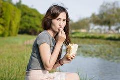A menina feliz e come o pão Foto de Stock