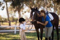 Menina feliz e jóquei fêmea que afagam o cavalo imagem de stock