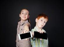 A menina feliz e o menino infeliz, crianças mostram a tela do telefone celular Fotos de Stock