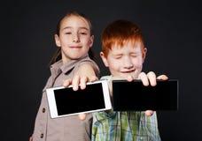 A menina feliz e o menino infeliz, crianças mostram a tela do telefone celular Fotos de Stock Royalty Free