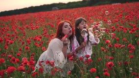 A menina feliz e sua mamã inflam bolhas de sabão no campo de florescência de papoilas vermelhas, movimento lento filme