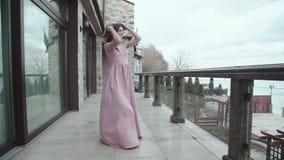 Menina feliz em caminhadas de sopro do vestido de noite no balcão na vista bonita video estoque