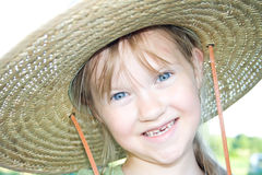 Menina feliz em um chapéu de palha com expressão engraçada. Imagem de Stock