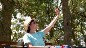 A menina feliz em um chapéu e em óculos de sol fotografa-se pelo telefone, sentando-se em um banco de parque video estoque
