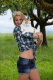 Menina feliz em um prado da flor do verão que guarda um gato imagens de stock