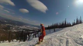 Menina feliz em um snowboard que desliza abaixo da inclinação video estoque