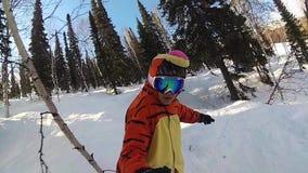 Menina feliz em um snowboard que desliza abaixo da inclinação vídeos de arquivo