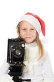 Menina feliz em um traje do Natal com câmera velha Foto de Stock