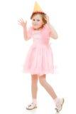 A menina feliz em um vestido e em um chapéu cor-de-rosa dança Foto de Stock Royalty Free