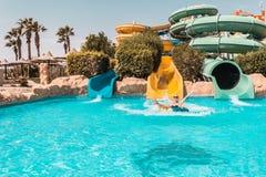 Menina feliz em uma corrediça de água na associação, tendo o divertimento durante férias de verão em um parque bonito da á fotos de stock