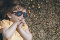 A menina feliz encontra-se na grama e olha-se o céu Nos óculos de sol nuvens refletidas Fotografia de Stock Royalty Free