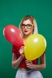 A menina feliz engraçada esconde atrás dos balões vermelhos e amarelos, a seguir de repente aparece e sorri extensamente olhando  Imagens de Stock