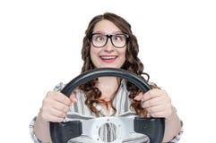Menina feliz engraçada nos vidros e olhos em um montão com a roda de carro, isolada no fundo branco, auto conceito foto de stock royalty free