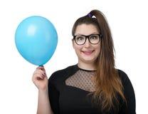 Menina feliz engraçada nos vidros com balão azul Fotografia de Stock