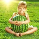 A menina feliz está abraçando a melancia enorme que senta-se no gree Imagem de Stock Royalty Free