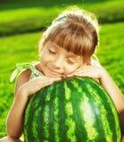 A menina feliz está abraçando a melancia enorme que senta-se no gree Foto de Stock Royalty Free