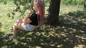 A menina feliz está balançando em um celeiro em um jardim rústico - movimento lento video estoque