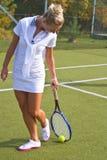 A menina feliz está com a raquete na corte no dia de verão ensolarado Fotos de Stock