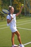 A menina feliz está com a raquete na corte no dia de verão ensolarado Imagens de Stock Royalty Free
